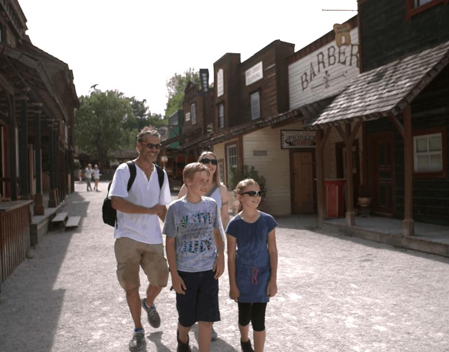 familie geht im erlebnispark durch eine westernstadt