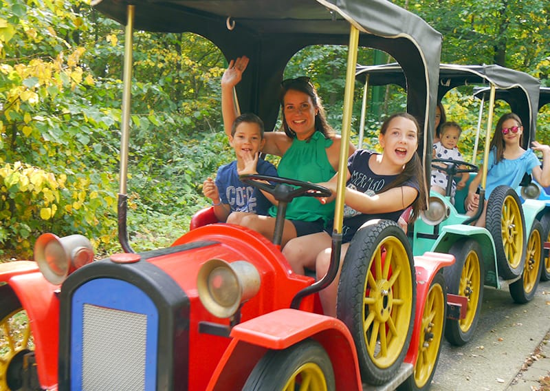 kinder und eltern sitzend in oldtimer autos durch den Freizeitpark schloss thurn