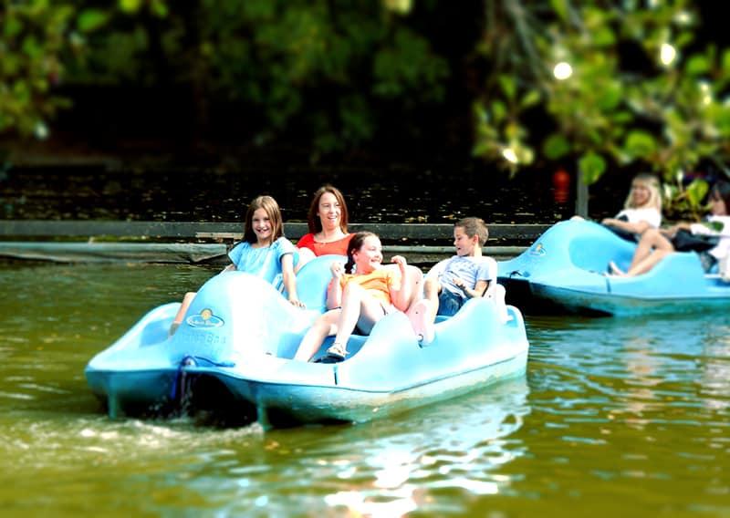 mutter mit drei kindern fahren im blauen tretboot